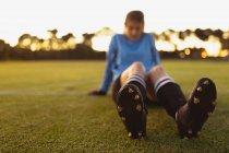 Первый вид уставшей кавказской футболистки, отдыхающей на траве на спортивной площадке — стоковое фото