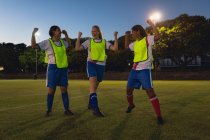 Front view of diverse female soccer players cheering at sports field after victory — Stock Photo