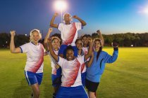 Front view of diverse female soccer team cheering on their victory at sports field — Stock Photo