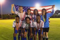 Front view of diverse female soccer team posing with American flag at sports field — Stock Photo