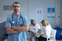 Vorderansicht eines kaukasischen Chirurgen mit gekreuztem Arm und Stethoskop um den Hals, der im Krankenhaus in die Kamera blickt — Stockfoto