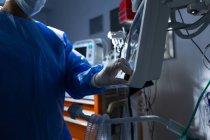Mixed-Race-Chirurgin mit Operationsmonitor im Operationssaal des Krankenhauses — Stockfoto