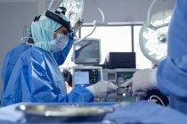 Vue latérale de divers chirurgiens pratiquant une chirurgie en salle d'opération à l'hôpital . — Photo de stock