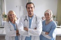 Frontansicht verschiedener Ärzte, die mit gekreuzten Armen auf der Station im Krankenhaus stehen — Stockfoto