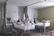 Overview of diverse doctors interacting with patients in the ward at hospital — Stock Photo