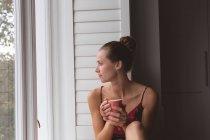 Vista frontale della donna caucasica con tazza di caffè guardando attraverso la finestra a casa — Foto stock