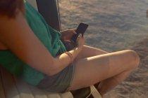 Пол розділ жінки за допомогою мобільного телефону на передньому сидінні кемпер Ван на пляжі — стокове фото