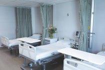 Moderne Krankenhausstation mit leeren Betten, medizinischem Monitor, grünen Vorhängen, Schränken und Blumen. — Stockfoto