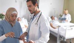 Vista lateral de diversos médicos discutiendo sobre el portapapeles en el pabellón en el hospital. En el fondo, la doctora caucásica discute los rayos X con pacientes de raza mixta de alto rango. - foto de stock