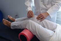 Partie médiane du médecin féminin utilisant un rouleau de mousse sur la jambe du patient féminin à l'hôpital — Photo de stock