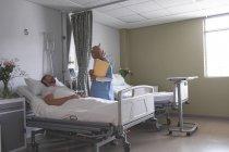 Вид з боку змішаних раси жіночий лікар взаємодіючих з Кавказького чоловічого пацієнта в палаті у лікарні — стокове фото