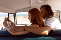 Side view of young Caucasian couple taking selfie with mobile phone in front seat of camper van at beach — Stock Photo