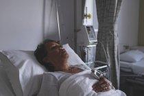 Verticale du patient féminin mélangé mûr de course dormant dans le lit dans la salle à l'hôpital — Photo de stock