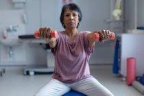 Обзор пациентов смешанной расы с гантелями на тренировочном мяче в больнице — стоковое фото