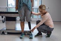 Vue avant du physiothérapeute féminin caucasien ajustant la jambe prothétique du patient féminin dans l'hôpital — Photo de stock