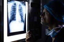 Вид збоку красивий молодий Кавказького чоловічого хірурга вивчення x-Ray на світлому полі в операційний театр в лікарні. — стокове фото