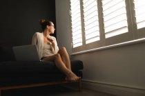 Вид збоку кавказька жінка дивиться через вікно під час використання ноутбука у вітальні будинку — стокове фото