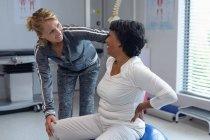 Vue latérale du physiothérapeute féminin caucasien aidant la patiente métisse sur le ballon d'exercice à l'hôpital — Photo de stock