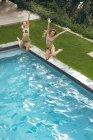 Вид на счастливых подруг, прыгающих в бассейне на заднем дворе — стоковое фото