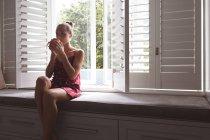 Vista frontal da bela mulher caucasiana bebendo café enquanto sentada no assento da janela no quarto em casa — Fotografia de Stock