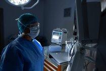 Вид збоку молодих змішаних раси жіночий хірург дивлячись на моніторі в операційний театр. Хірург носить хірургічна маска, рукавички, плаття, шапочка, захисні окуляри. — стокове фото