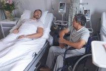 Vue de face de divers patients masculins interagissant les uns avec les autres dans le service de l'hôpital . — Photo de stock