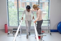 Front view of Caucasian female physiotherapist helping mixed-race female patient walk with parallel bars in the hospital — Stock Photo