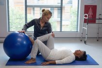 Side view of Caucasian female physiotherapist helping mixed-race female patient with exercise on exercise ball in the hospital. — Stock Photo