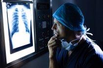 Seitenansicht eines hübschen jungen kaukasischen Chirurgen bei der Untersuchung des Röntgenbildes auf einem Leuchtkasten im Operationssaal des Krankenhauses. — Stockfoto