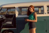 Vista laterale di bella donna caucasica appoggiata sul camper e utilizzando il telefono cellulare in spiaggia — Foto stock