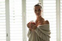 Ritratto di donna caucasica con tazza di caffè che guarda la macchina fotografica a casa — Foto stock