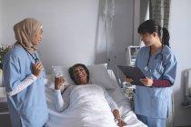 Vue avant de diverses médecins féminines interagissant avec le patient féminin mûr de course mixte dans le service à l'hôpital. Le patient féminin regarde heureux. — Photo de stock