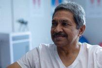 Vista anteriore del paziente maschio felice razza mista guardando lontano in ospedale — Foto stock