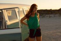 Vista frontale di bella giovane donna caucasica con le mani sul fianco guardando lontano vicino camper in spiaggia — Foto stock