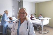 Retrato de una doctora caucásica sonriendo en la sala del hospital. En el fondo diversos médicos están interactuando con sus pacientes al lado de las camas . - foto de stock