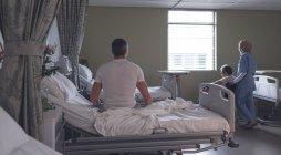 Заднього виду Кавказького чоловічого пацієнта сидять на ліжку і змішаної раси жіночий лікар в хіджабі з інвалідів старший змішані раси чоловічого пацієнта в палаті у лікарні — стокове фото