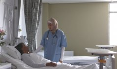 Side view of beautiful mixed-race female nurse in hijab interacting with mixed-race female patient in the ward at hospital. Nurse has stethoscope around her neck. — Stock Photo