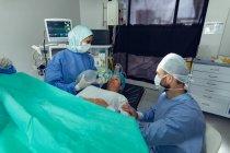 Hochwinkelaufnahme eines kaukasischen Mannes, der schwangere Frau während der Wehen tröstet, während gemischte Ärztin Beatmungsgerät bei Patientin im Operationssaal des Krankenhauses einsetzt — Stockfoto