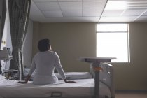 Rear view of mixed-race female patient sitting on bed while looking outside in the ward at hospital — Stock Photo