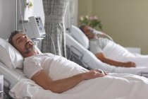 Portrait of Caucasian male patient relaxing in bed in the ward at hospital — Stock Photo