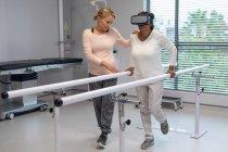 Seitenansicht einer kaukasischen Patientin mit Virtual-Reality-Headset, während eine kaukasische Physiotherapeutin ihr beim Gehen mit parallelen Stangen im Krankenhaus hilft — Stockfoto