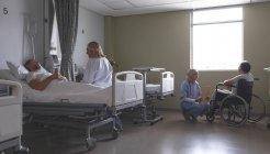 Vista lateral da médica branca que interage com a paciente caucasiana que está deitada na cama na enfermaria do hospital. Enfermeira feminina de raça mista no hijab discutindo pasta médica com paciente mestiço sênior em cadeira de rodas ao lado da janela . — Fotografia de Stock