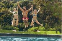 Вид з днем кавказьких чоловічих і жіночих друзів стрибки в басейні на задньому дворі — стокове фото