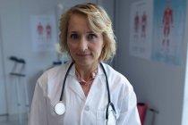Retrato de hermosa doctora caucásica mirando la cámara en el hospital - foto de stock
