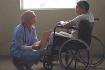 Vue latérale d'une patiente de race mixte qui interagit avec un patient âgé de race mixte handicapé en fauteuil roulant à l'hôpital . — Photo de stock