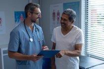 Vorderansicht eines kaukasischen Chirurgen, der mit einem älteren Mischlingspatienten im Krankenhaus interagiert — Stockfoto