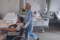 Seitenansicht einer Mixed-Race-Ärztin im Hijab, die einen älteren Mixed-Race-Patienten im Rollstuhl im Krankenhaus schubst. — Stockfoto