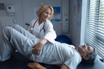 Opinião dianteira o doutor fêmea caucasiano que examina o paciente masculino sênior da misturado-raça para trás no hospital — Fotografia de Stock