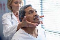 Vue de face du médecin féminin caucasien examinant le cou de patient masculin métis à l'hôpital — Photo de stock