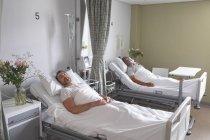 Вид збоку різних чоловічих пацієнтів, що сплять в ліжку в палаті в лікарні — стокове фото